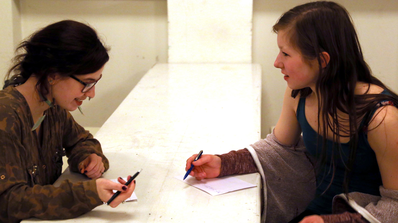 Zwei Mädchen bei der Produktion biografischer Texte in einer Schreibwerkstatt zum biografischen Theater.