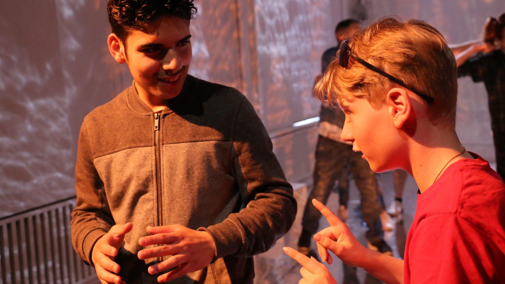 zwei Jungen diskutieren miteinander zum Thema Glaube im Heimathafen Neukölln